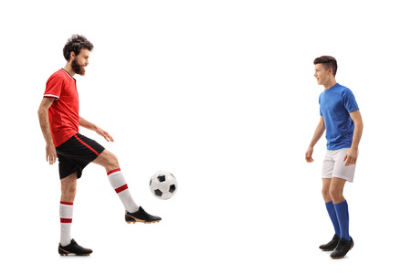 Full length profile shot of a father and his son dressed in jerseys passing a football isolated on white background Stock Photo