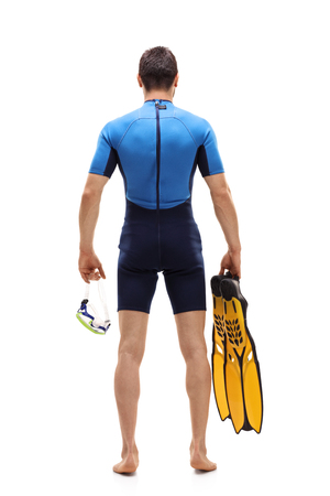 Full length rear view shot of a man in a wetsuit holding a diving mask and swimming fins isolated on white background Stock Photo