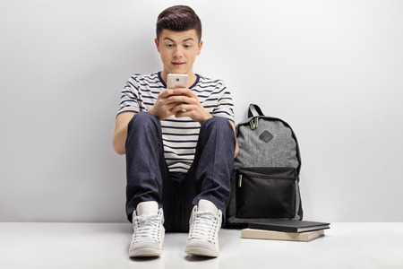 Teenage student leaning against a white wall and using a phone Фото со стока