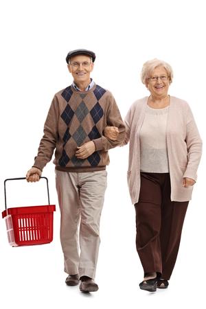 Full length portrait of a joyful senior couple with an empty shopping basket walking towards the camera isolated on white background