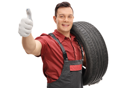 Young mechanic with a tire and making a thumb up sign isolated on white background Stock Photo