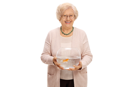 fish tank: Mature woman holding a bowl with a goldfish inside and looking at the camera isolated on white background Stock Photo
