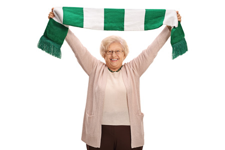 Overjoyed elderly football fan holding a scarf isolated on white background