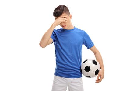 白い背景に分離された信じられない思いで頭を抱えた動揺十代のフットボール選手 写真素材