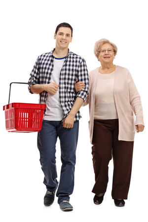 Full length portrait of a young guy with a shopping basket and a mature woman walking towards the camera isolated on white background