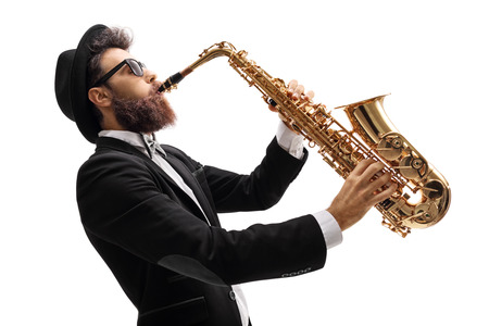 Profile shot of a man in a suit playing on a saxophone isolated on white background Foto de archivo