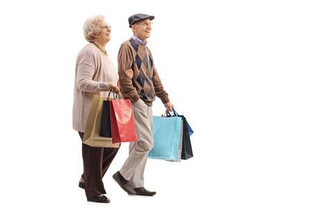 シニア夫婦の分離ホワイト バック グラウンドを歩いてショッピング バッグとの完全な長さのプロファイル ショット