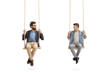 background person: Father and son sitting on swings and looking at each other isolated on white background Stock Photo
