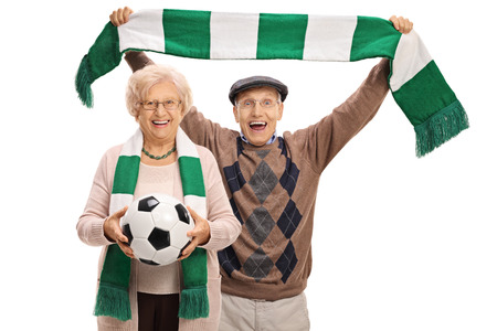 Overjoyed elderly soccer fans with a football and a scarf isolated on white background
