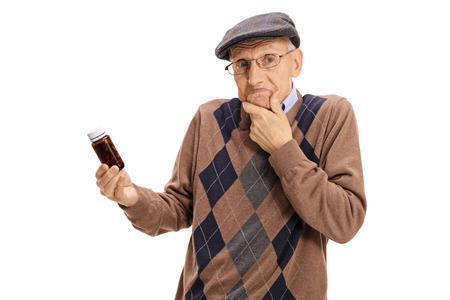 Confused senior tenant une bouteille de pilules isolé sur fond blanc Banque d'images - 76713469