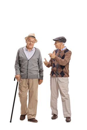 Full length portrait of two elderly men walking towards the camera and talking to each other isolated on white background 版權商用圖片