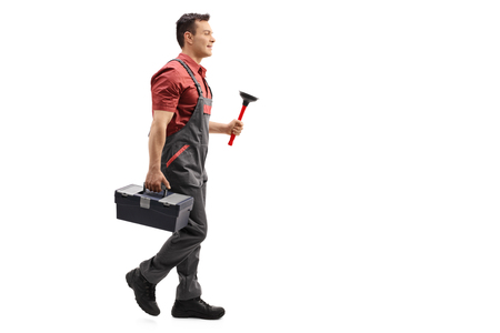 man profile: Full length profile shot of a plumber holding a plunger and a toolbox walking isolated on white background