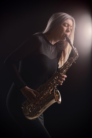 onstage: Female jazz musician playing a saxophone during a concert Stock Photo
