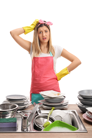 Upset young woman behind a sink filled with dirty plates isolated on white background Stock Photo