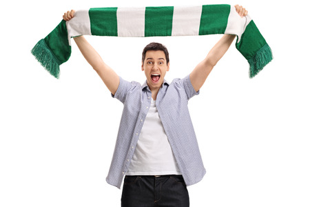 Overjoyed football fan holding a scarf and cheering isolated on white background