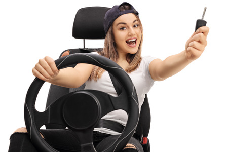 Joyful teenage girl with a car key sitting in a car seat isolated on white background Stock Photo