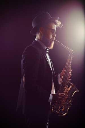 onstage: Profile shot of a bearded man performing on a saxophone Stock Photo
