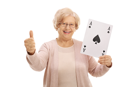 Joyful mature woman showing an ace of spades card and making a thumb up gesture isolated on white background Stock Photo
