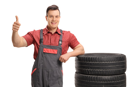 dungarees: Mechanic leaning on a stack of tires and making a thumb up sign isolated on white background