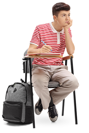 Bored teenage student sitting in a school chair isolated on white background Imagens