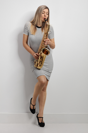 Full length portrait of a young woman in a dress playing a saxophone and leaning against a wall Stock Photo