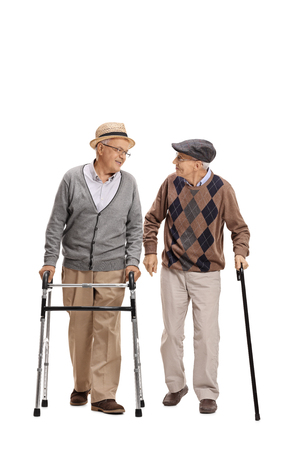 Full length portrait of an elderly man with a walker and another man with a cane walking towards the camera isolated on white background