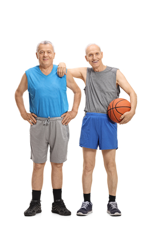 Full length portrait of two elderly men in sportswear with one of them holding a basketball isolated on white background Stock Photo
