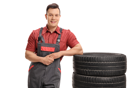 dungarees: Mechanic leaning on a stack of tires and looking at the camera isolated on white background