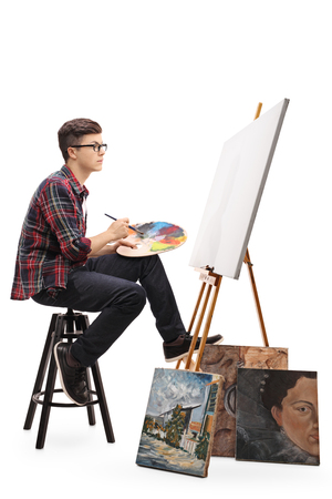 Profile shot of a teenage painter with a paintbrush and a palette looking at a blank canvas isolated on white background