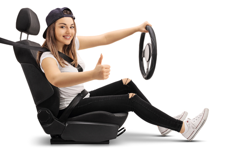 fastened: Teenage girl in a car seat holding a steering wheel and making a thumb up sign isolated on white background
