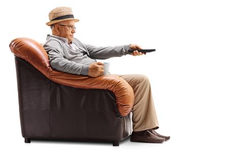 Verveelde bejaarde man die een kopje en een afstandsbediening in een leunstoel houdt en televisie kijkt die op een witte achtergrond wordt geïsoleerd