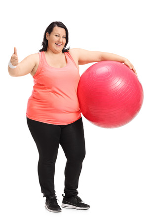 Full length portrait of a happy overweight woman holding a pilates ball and making a thumb up sign isolated on white background Stock Photo