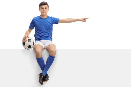 Teenage football player sitting on a panel and pointing right isolated on white background Stock Photo