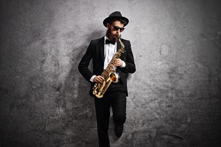 Jazz musician playing a saxophone and leaning against a rusty gray wall 版權商用圖片
