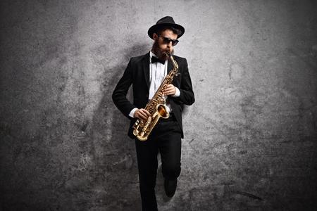 Jazz musicien joue un saxophone et s'appuie contre un mur gris rouillé Banque d'images - 77836151