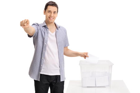 Voter casting a vote into a ballot box and pointing at the camera isolated on white background