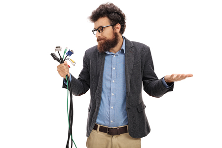 bearded wires: Confused man holding different types of electronic connectors isolated on white background