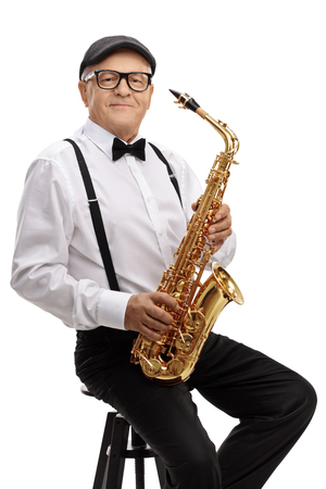 Mature jazz musician with a saxophone sitting on a chair isolated on white background