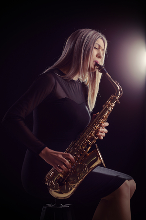 onstage: Female jazz musician sitting on a chair and playing a saxophone during a concert