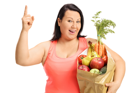 Happy overweight woman with a paper bag filled with groceries holding her finger up isolated on white background