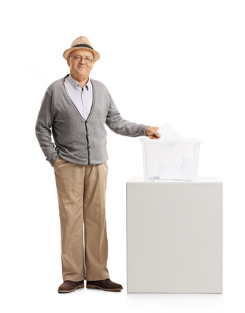 Full length portrait of a senior casting a vote into a ballot box isolated on white background