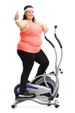Full length portrait of an overweight woman exercising on a cross trainer machine and making a thumb up sign isolated on white background Stock Photo