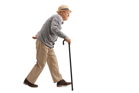 Tiro de perfil de longitud completa de un senior caminando con un bastón aislado en fondo blanco Foto de archivo
