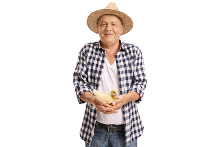 Elderly farmer holding a small duckling and looking at the camera isolated on white background