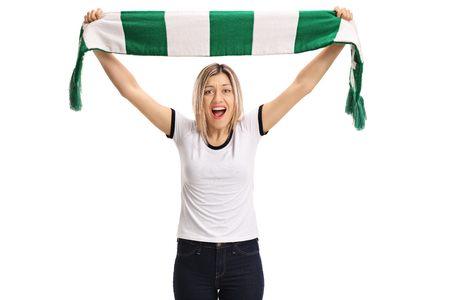 Delighted female football fan holding a scarf and cheering isolated on white background
