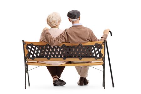 白い背景の上のベンチに座っている老夫婦の背面ビュー ショットが分離されました。 写真素材