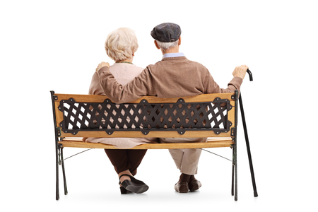 Rear view shot of a senior couple sitting on a bench isolated on white background