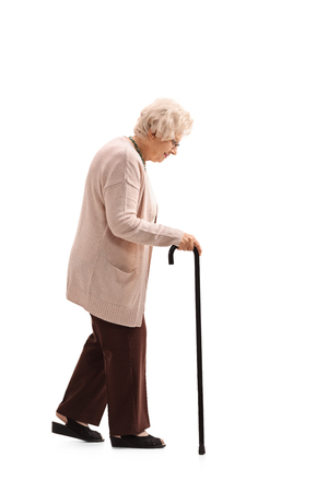 Full length profile shot of an elderly woman with a walking cane isolated on white background