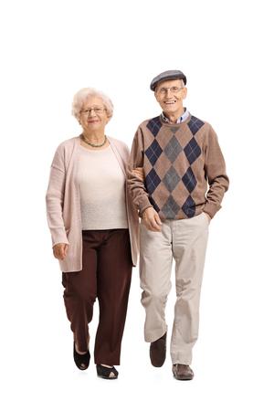 白い背景に分離されてカメラに向かって歩く老夫婦の完全な長さの肖像画