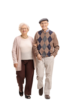 Full length portrait of an elderly couple walking towards the camera isolated on white background